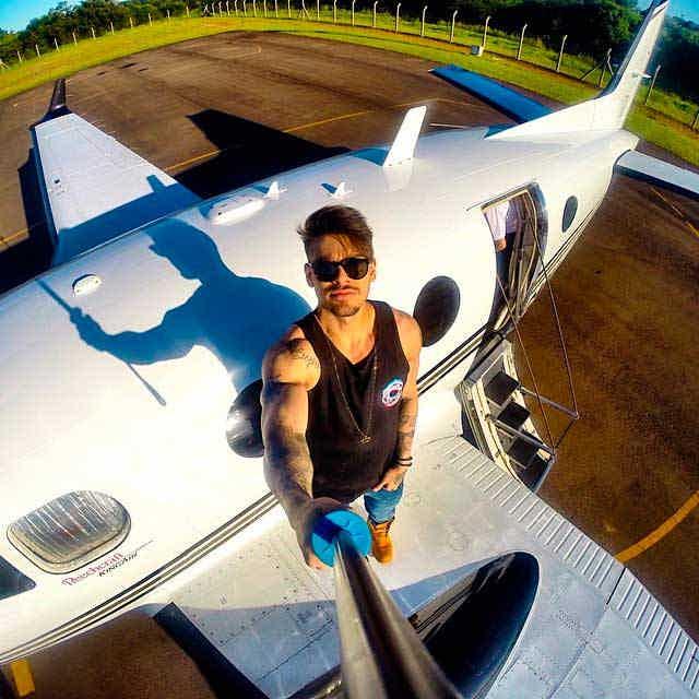 Lucas Lucco tirando uma selfie em pé na asa de seu avião particular