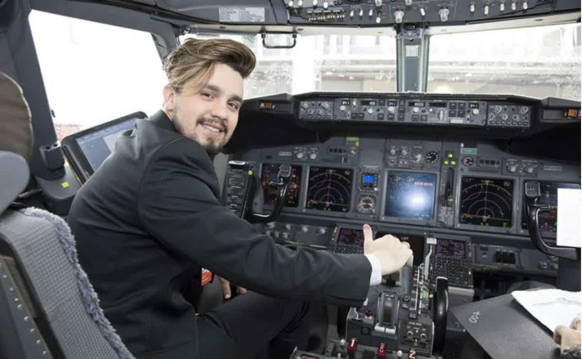 Luan Santana sentado e sorrindo na cabine de comando de seu avião particular