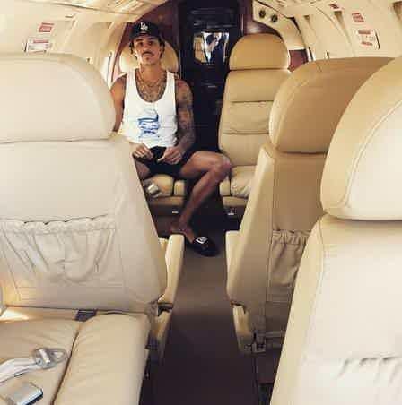MC Livinho sentado na poltrona de seu avião particular de luxo