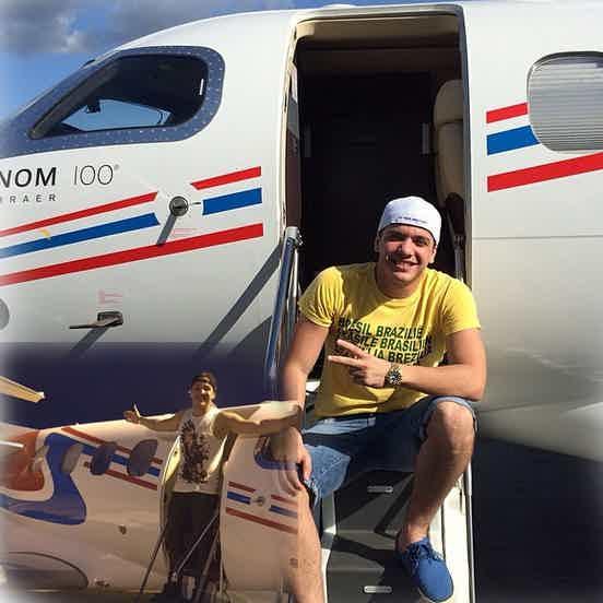 Wesley Safadão sorrindo sentado na entrada de seu avião particular